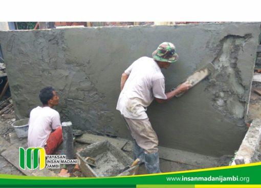 relawan sedang membantu pekerjaan pembangunan MCK warga